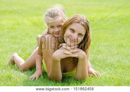 Mum And Daughter Lie On A Green Lawn In A Bikini And Look In The Frame