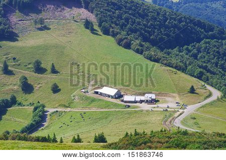 Summer view in french Vosges above Grand Ballon.Green fields meadows barns roads and forest. Mountainous green scenery in Alsace village in summer sunny day.