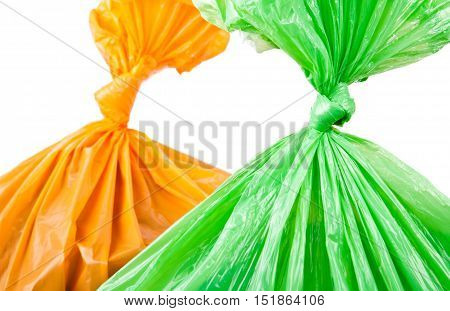 Green and orange garbage bags on white background