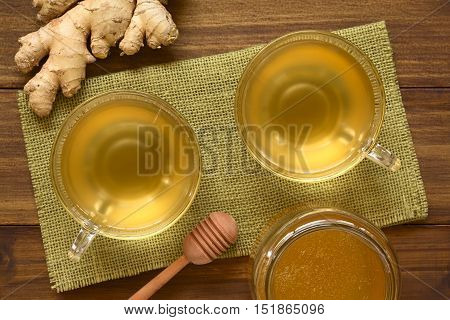 Hot ginger tea in glass cups with honey and raw ginger on the side photographed overhead on wood with natural light (Selective Focus Focus on the tea and cups)