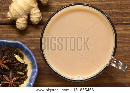 Homemade Indian Masala Chai Tea made of black tea a variety of spices and mixed with milk photographed overhead on dark wood with natural light (Selective Focus Focus on the top of the tea)