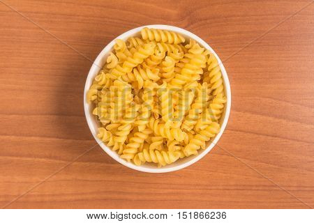 Fusilli Into a bowl over a wooden table