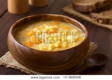 Vegetarian and vegan yellow split pea soup or stew with potato carrot and celery in wooden bowl photographed with natural light (Selective Focus Focus one third into the soup)