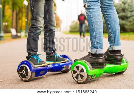 Feet Of Girl And Boy Riding Electric Mini Segway Outdoors In Park.
