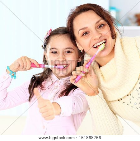 Mother and daughter brush their teeth in bathroom