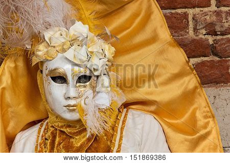 VENICE, ITALY - FEBRUARY 15, 2015: Portrait of an unidentified woman wearing a gold costume and posing at Venice carnival