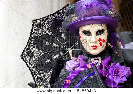 VENICE, ITALY - FEBRUARY 15, 2015: An unidentified woman in a violet and black costume, posing with an umbrella at Venice Carnival