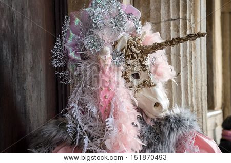 VENICE, ITALY - FEBRUARY 15, 2015: An unidentified person wearing a magnificent unicorn mask, posing at the Carnival of Venice