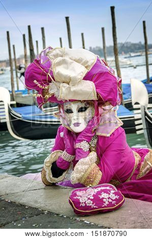 VENICE, ITALY - FEBRUARY 15, 2015: An unidentified person on a pink costume posing close to a series of gondolas during the Carnival of Venice