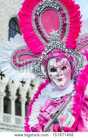VENICE, ITALY - FEBRUARY 15, 2015: A model disguised with a white and pink costume playing violin at Venice carnival
