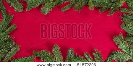 Red cloth showing wood grain underneath with complete evergreen border.