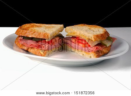 Sliced Ham Sandwich on a white Plate with Black Background