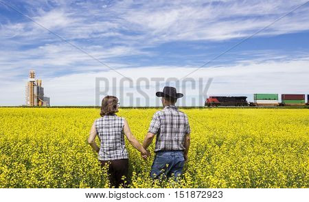 horizontal image of a husband and wife checking canola field while a train rumbles by in the background next to a grain elevator.