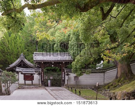 Kyoto Japan - September 16 2016: The humble entrance gate to the Shorenin Buddhist Temple is set at the edge of a formal garden with large trees. Pay gray wall and dark wooden structure.