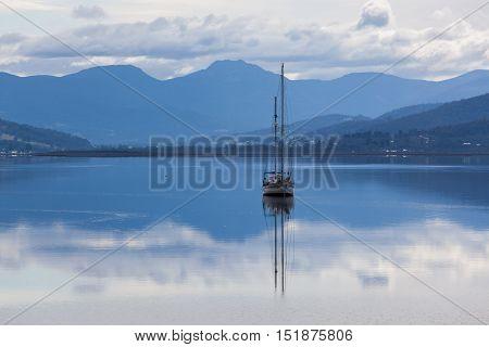 Sailboat Reflecting In Calm Waters Of Huon River, Tasmania