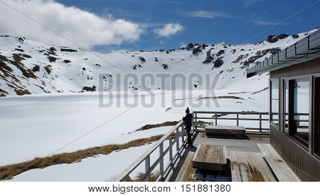 A Woman At The Lake Angelus Hut Enjoys Mountain Views.  Nelson Lakes National Park, Southern Alps, New Zealand.