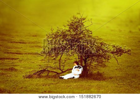 Pregnant woman sitting alone under a beautiful tree in autumn with the concept of time loneliness pregnancy and expectations