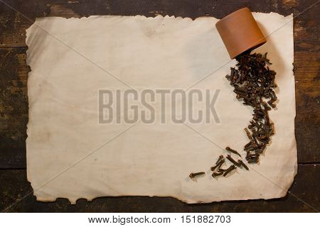 Cloves spice is scattered on a sheet of old paper