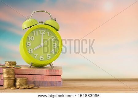 clock with money on desk in nature background. concept of time is money save time Investment term.
