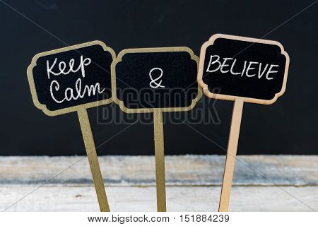 Keep Calm And Believe Message Written With Chalk On Mini Blackboard Labels