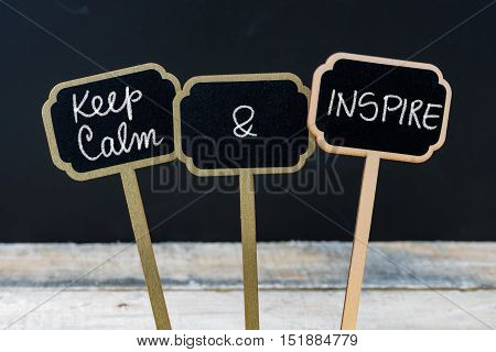 Keep Calm And Inspire Message Written With Chalk On Mini Blackboard Labels