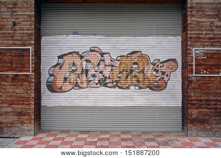 Corrugated metal sheet background, Street art of graffiti painted with spray paint on white painted Slide door on wooden walls, two empty frames on both sides. Urban contemporary culture.