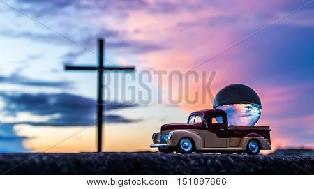 Pickup truck with a glass ball on it with a black cross in side it.
