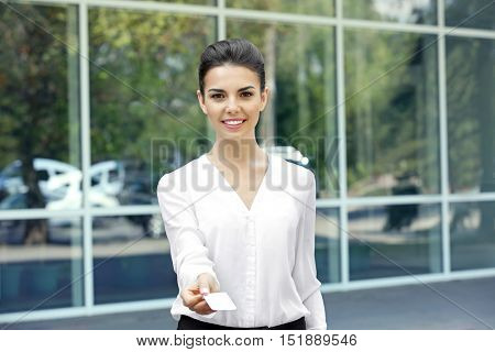 Businesswoman giving business card on window background