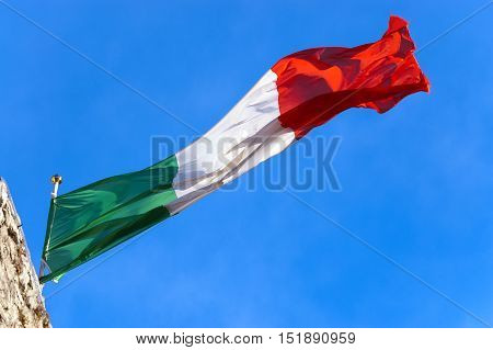 National Italian flag with pole flowing in the wind on a clear blue sky