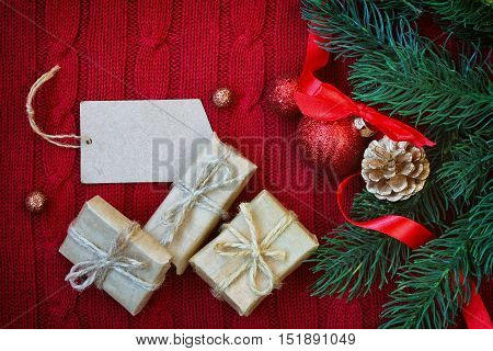 Christmas red knitted background with branch fir blank paper tag new year ball on ribbon gift golden pine cone