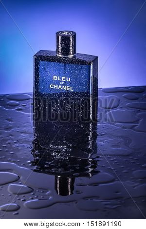 Bangkok, Thailand - November 14, 2014 : Perfume in blue bottle with water droplets.