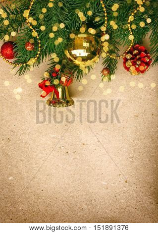 Vintage Christmas card with fir tree branch bell ball on rough paper background