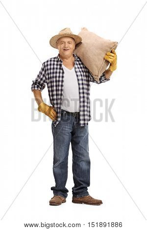 Full length portrait of a mature farmer holding a burlap sack isolated on white background