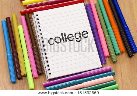 Felt-tip pen and notepad on a wooden background and college text concept