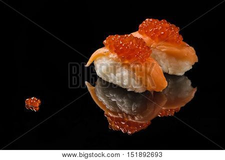 Sushi and red caviar on black acryle with reflection