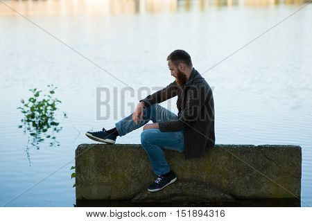 sad young man with a beard sitting on a background of a pond