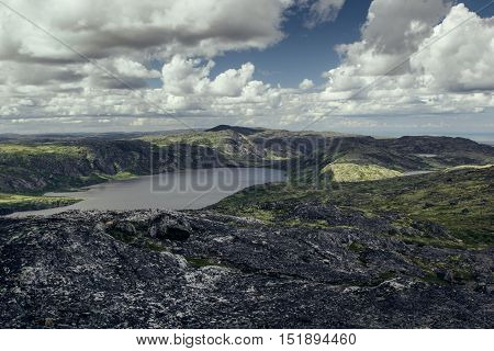 Highlands valley with views of the lake and the green hills in sunny cloudy day. Arctic summer the tundra Norway.