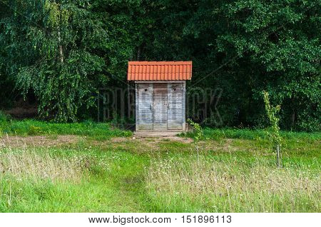 Outdoor toilet in a meadow next to the forest