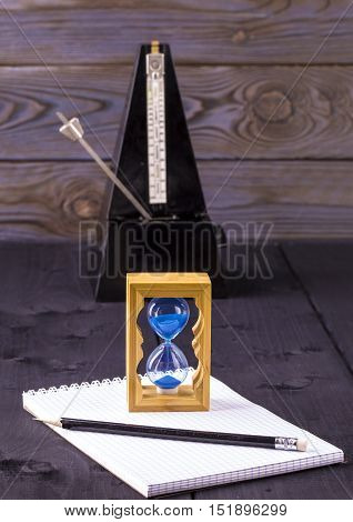 hourglass metronome and memo pad with a pencil on a wooden table
