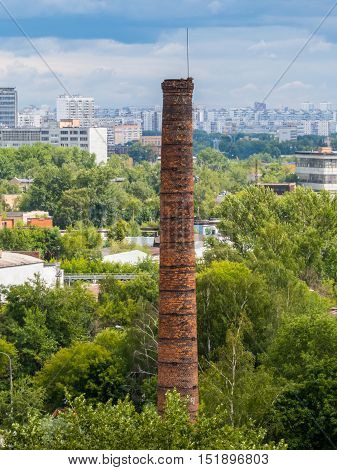 Old brick chimney on the background of the city
