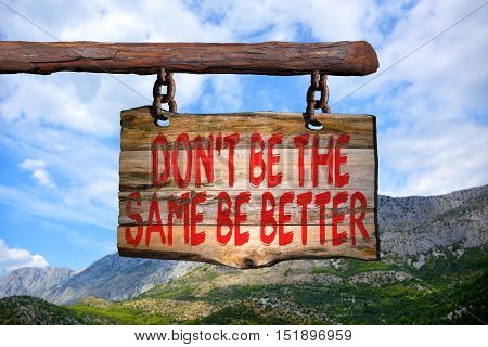 Don't be the same be better motivational phrase sign on old wood with blurred background