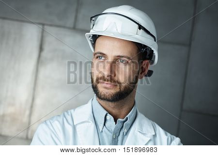 Portrait of confident young engineer wearing protective hardhat.