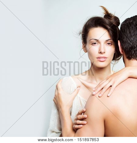 young sexy couple of muscular man embracing with back and pretty woman or girl with brunette hair in white blouse in studio on grey background copy space