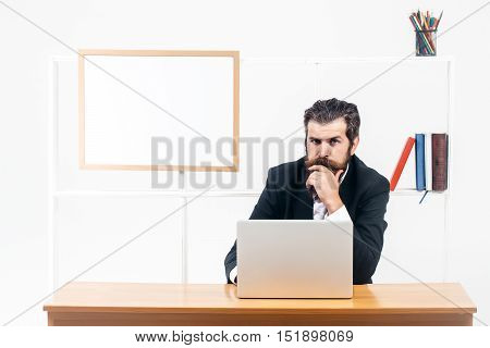 Serious bearded businessman in black suit thinks sitting at desk with laptop in office