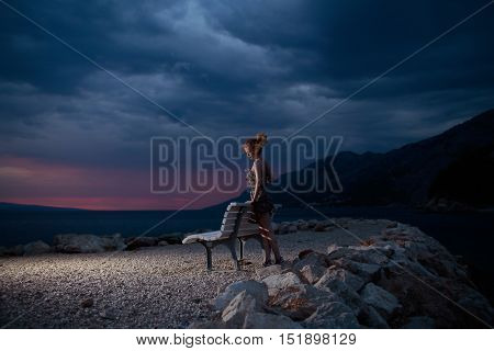 pretty sexy woman or girl with wine glass near bench outdoor over dark twilight sky with clouds on beach with sea or ocean water on evening natural background
