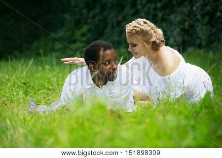 Romantic couple of man handsome african American and pretty girl embrace on green grass on summer day