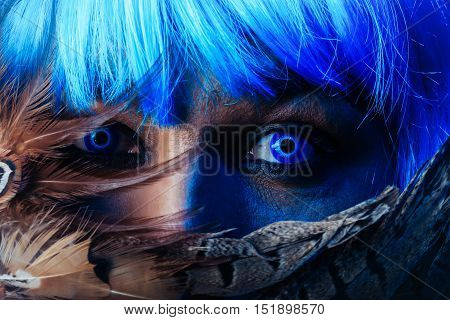 handsome man with blue eyes in fashion wig behind brown feathers
