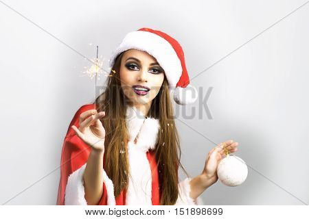 young santa claus woman with glamour makeup on pretty face with long hair in red and white christmas or new year coat and hat holding winter holiday decoration and sparkler and bengal fire