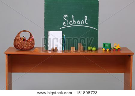 Text school on green blackboard wicker basket with colorful colored pencils paper white notebook wooden cubes apples and car toy on desk on gray background studio