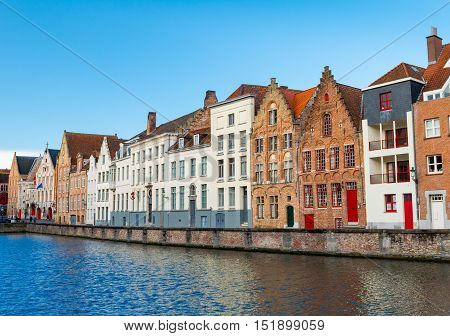 Bruges (Brugge) - February of 2016, Belgium: Typical belgian street with traditional medieval brick houses and water canal